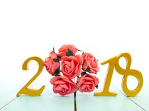 A golden new year 2018 banner and a bouquet of roses. On pale blue wooden background royalty free stock photos
