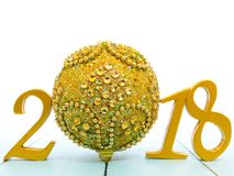 A golden new year 2018 banner and a golden christmas ball. On pale blue wooden background stock photos