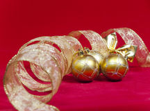 Golden New Year's balls and ribbon on a red background Royalty Free Stock Photography