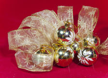 Golden New Year's balls and ribbon on a red background Royalty Free Stock Image