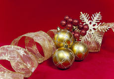 Golden New Year's balls and ribbon on a red background Royalty Free Stock Photos