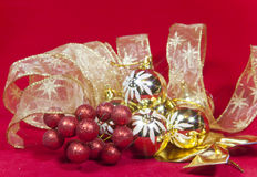 Golden New Year's balls and ribbon on a red background Royalty Free Stock Images