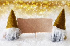 Golden Noble Gnomes With Card, Copy Space. Christmas Greeting Card With Two Golden Gnomes. Sparkling Bokeh And Noble Background With Snow. Copy Space For Royalty Free Stock Photography