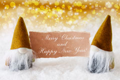 Golden Noble Gnomes With Card, Merry Christmas Happy New Year. Christmas Greeting Card With Two Golden Gnomes. Sparkling Bokeh And Noble Background With Snow Stock Photo
