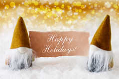 Golden Noble Gnomes With Card, Text Happy Holidays. Christmas Greeting Card With Two Golden Gnomes. Sparkling Bokeh And Noble Background With Snow. English Text Royalty Free Stock Photography