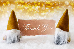 Golden Noble Gnomes With Card, Text Thank You. Christmas Greeting Card With Two Golden Gnomes. Sparkling Bokeh And Noble Background With Snow. English Text Thank Stock Images