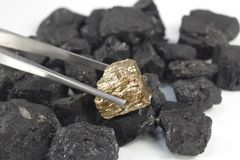 Golden nugget on coals background Stock Photo