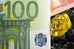 Golden nugget on euro banknotes with raw coal Stock Images