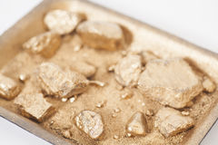 Golden nuggets on grungy wash pan with sand on white Royalty Free Stock Images