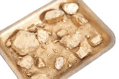 Golden nuggets on grungy wash pan with sand on white Stock Photos