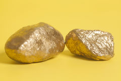 Golden nuggets on a yellow . Stock Images