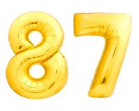 Golden number 87 eighty seven made of inflatable balloon. Isolated on white background Stock Photos