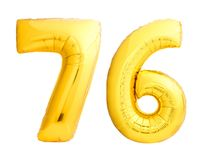 Golden number 76 seventy six made of inflatable balloon. Isolated on white background Royalty Free Stock Images