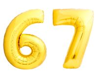 Golden number 67 sixty seven made of inflatable balloon. Isolated on white background Royalty Free Stock Photography