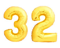 Golden number 32 thirty two made of inflatable balloon. Golden number 32 thirty two of inflatable balloon isolated on white background royalty free stock image