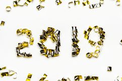 Golden numbers of confetti and foil tape. The new year 2019 on white background. Golden numbers of confetti and foil tape. The new year 2019. White background stock image