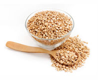 Golden oat flakes in bowl and spoon on white background Royalty Free Stock Images