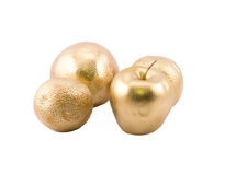 Golden objects - apple and three oranges Stock Photography