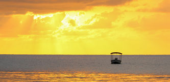 Golden ocean sunset with a boat silhouette Stock Images