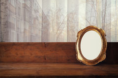 Golden old blank frame on window sill and urban view Royalty Free Stock Photo
