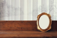 Golden old blank frame on wooden window sill Stock Image