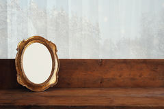 Golden old blank frame on wooden window sill Stock Photo
