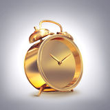 Golden old fashioned  alarm clock on grey  background. Royalty Free Stock Image