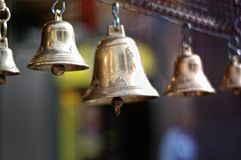 Golden old fashioned bells, Golden jingle bells with blurred background. Closeup of old fashioned golden jingle bells being sold in a Sunday market in Florence royalty free stock image