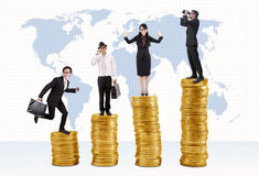 Golden opportunity. Business success concept: Businessmen and businesswoman standing on stacks of golden coins Stock Photos