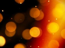 Golden orange glow on a black background with round blurred lights and bright sparkles stock images