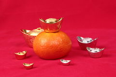 Golden orange with silver and gold of silver ingots . Royalty Free Stock Photo