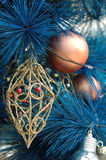 Golden ornament on blue christmas tree. Close up of golden ornament on blue christmas tree Stock Images