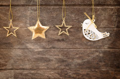 Golden ornaments hanging over wooden background Royalty Free Stock Image