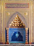 Golden ornate arched mihrab niche with floral pattern, blue Turkish ceramic tiles and arabic calligraphy, Cairo, Egypt Stock Photos