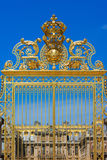 Golden ornate gates of the Palace of Versailles over blue sky. P Royalty Free Stock Image