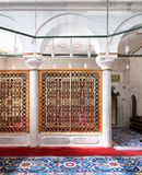 Golden ornate perforated partition framed in white marble arch and ornate carpet Royalty Free Stock Images