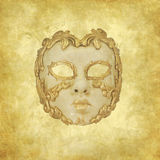 Golden ornated Venetian mask on grunge background. Golden vintage Venetian mask on a retro golden texture royalty free stock photo
