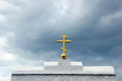Golden orthodox cross closeup. On background of cloudy sky Stock Photography