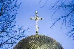 Golden orthodox cross on the dome of the church.  stock photo