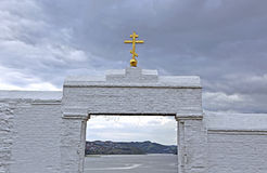 Golden orthodox cross. At the gate of the ancient monastery on background of cloudy sky Royalty Free Stock Images