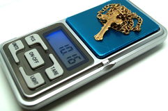 The golden orthodox cross lies on the digital scales jewelry scales. The Golden Orthodox Christian Cross lies on the digital jewelry scales Stock Image