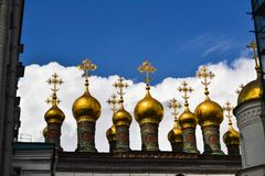 Golden Orthodox crosses and domes of the Church of the Nativity Verkhospasskiy Sobor at Kremlin, Moscow with blue sky.  stock photo