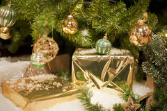 Golden Package under Christmas Tree Stock Images