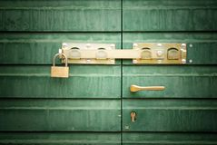 Golden padlock and handle on green door, detail. Golden lock, padlock and handle on green door, detail Royalty Free Stock Images