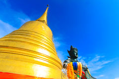 Golden pagoda with blue sky and holy religious statue Stock Photography