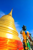Golden pagoda with blue sky and holy religious statue Royalty Free Stock Photography