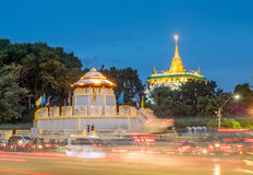 Golden pagoda with traffic light movement. Golden mountain pagoda and old style fortress decorated with light bulb with night light traffic movement under Stock Photography