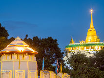 Golden pagoda with traffic light movement. Golden mountain pagoda and old style fortress decorated with light bulb with night light traffic movement under Stock Images