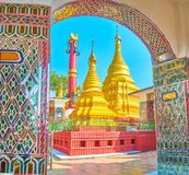 The golden pagodas on Mandalay Hill, Myanmar. The view on the courtyard of Su Taung Pyae Temple with golden pagodas through the arcade of covered gallery royalty free stock photos
