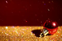 Golden paillettes and Christmas ball against color background. stock image